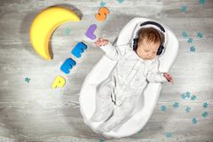 Newborn baby sleeps in a special orthopedic mattress Baby cocoon, on a wooden floor multicolored letters around. Calm. Newborn baby quietly sleeps in a special stock photography