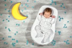 Newborn baby sleeps in a special orthopedic mattress Baby cocoon, on a wooden floor, toy moon and puzzles around. Calm. Newborn baby quietly sleeps in a special royalty free stock photos