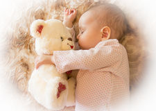 Newborn baby sleeps with a teddy bear Stock Photography