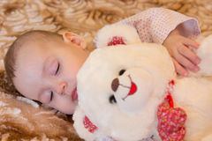 Newborn baby sleeps with a teddy bear Stock Photos