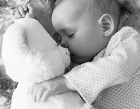 Newborn baby sleeps with a teddy bear black and white.  stock images