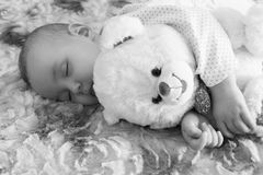 Newborn baby sleeps with a teddy bear black and white.  royalty free stock photos