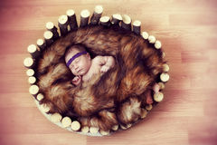Newborn baby sleeps in a wooden cradle Stock Image