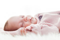 Newborn baby slepping on white fur blanket. Stock Photo