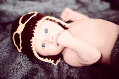 Newborn baby in a small pilot cap lying on blanket Stock Photo