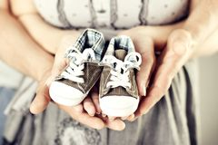 Newborn Baby Sneakers in Family Hands, Parents Holding New Born Kids Booties royalty free stock photos