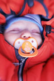 Newborn baby with soother in winter clothes.  stock photography
