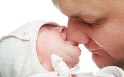Newborn baby sucking father nose stock photography