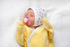 Newborn baby sucking a pacifier Stock Photos
