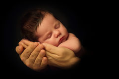 Newborn Baby taken closeup in father`s Hand - black and white.  stock photography
