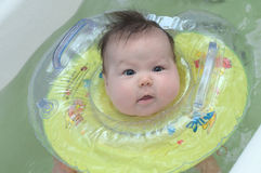 Newborn baby taking a bath with a rubber ring royalty free stock photos