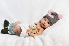 Newborn baby with teddy bear in a knitted hat Stock Photos
