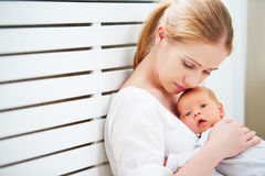 Newborn baby in tender embrace of mother Stock Photo