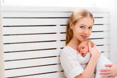 Newborn baby in tender embrace of mother Stock Photos
