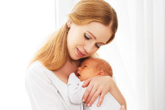 Newborn baby in tender embrace of mother Stock Image