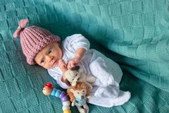 Newborn baby with toys in bed. Baby girl in wool hat looks suspiciously stock image