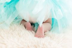 Newborn baby in turquoise dress back shot. Legs in focus Stock Photos