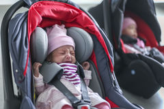 Newborn baby twins girl sitting in a car seat Stock Photos