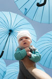 Newborn baby under a blue umbrellas. Royalty Free Stock Photography