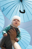 Newborn baby under a blue umbrellas. Royalty Free Stock Photos