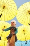 Newborn baby under a yellow umbrellas. Stock Images