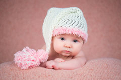 Newborn baby in a warm knitted hat. Stock Photo