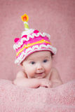 Newborn baby in warm knitted hat the form of cake with a candle.  Stock Photos