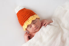 Newborn Baby Wearing a Halloween Candy Corn Hat Stock Photo