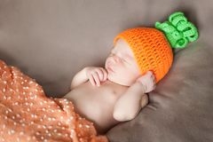 Newborn baby wearing a knitted carrot or pumpkin hat Stock Photo