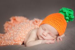 Newborn baby wearing a knitted carrot or pumpkin hat Royalty Free Stock Photo