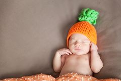 Newborn baby wearing a knitted carrot or pumpkin hat Stock Photos