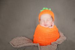 Newborn baby wearing a knitted carrot or pumpkin hat Royalty Free Stock Photos