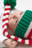 Newborn baby wearing a knitted Christmas hat. Newborn baby wearing a knitted Christmas elf hat Royalty Free Stock Image