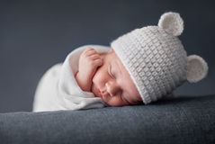 Newborn baby 2 weeks old sleeping on soft blue  fluffy blanket. With funky woolen hat Royalty Free Stock Photography