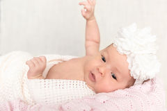 Newborn baby  with white headband laying in the basket Royalty Free Stock Image