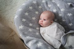 A newborn baby is lying on a gray bedspread and watching someone. A newborn baby in a white lace blouse lies on a gray bedspread with white stars and watches royalty free stock image