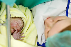 Newborn baby wrapped in blankets after birth. Mother looking for the first time on new born daughter. Newborn child seconds and minutes after birth. Happy mum Stock Images