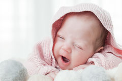 Newborn baby yawning lying on bed. Royalty Free Stock Image