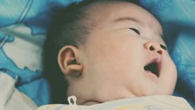 Newborn baby yawning and relaxing on the bed. Healthy children concept. Cinematic style colors. Close up face of a two-month adorable asian baby relaxing stock video