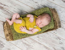 Newborn baby in yellow costume sleeping on wooden cot Stock Image
