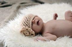 Newborn babygirl. Little newborn baby girl with hat on eyes Stock Photo