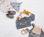 Newborn babys clothing, wooden beanbag and teether on marble background. Newborn baby`s clothing, wooden beanbag, teether and toy on light marble background with stock photography