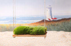 Newborn backdrop prop of a swing with moss. A backdrop photography prop image of a swing with moss with sand, a lighthouse and the ocean in the background Royalty Free Stock Images
