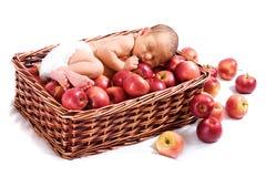 Newborn in the basket with apples. Newborn sleeping in the basket with apples royalty free stock image