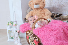 Newborn in basket, baby girl daughter. Cute decoration with pink blanket, candles, toy bear and hearts Royalty Free Stock Image