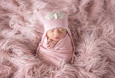 Newborn in beanie hat on a shaggy carpet. Sleepy newborn in a cute beanie hat on a pink shaggy carpet stock photography