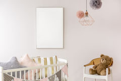 Newborn bedroom with white crib. Chair, copper lamp, teddy bear Royalty Free Stock Photos