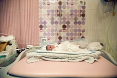 Newborn after birth with umbilical cord lies. On a white cloth diaper royalty free stock image