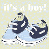 Newborn blue shoes with shoelaces for boy. It`s a boy! Vector illustration on blue hearts on yellow pattern background. Hand drawn cute newborn shoes for boy. It vector illustration
