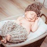 Newborn boy  asleep in the basket. Newborn boy in pants and hat asleep in the basket Stock Photo